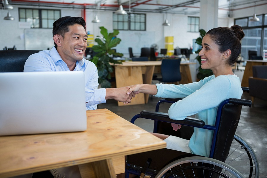 Businessman shaking hands with disabled colleague