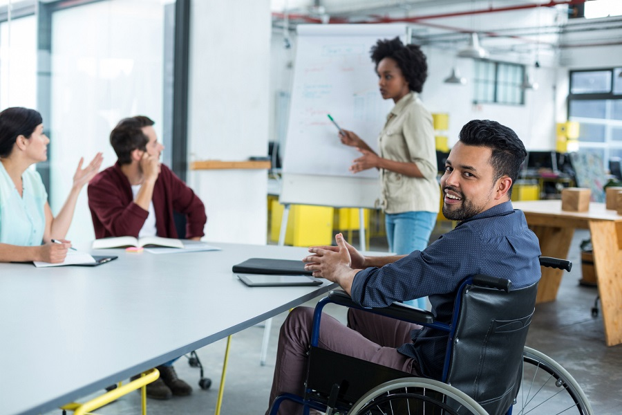 Smiling disabled business executive in wheelchair at meeting