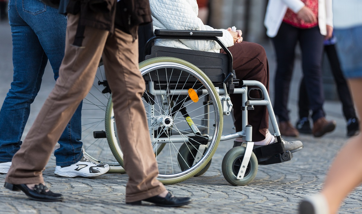 A Disabled Person On Wheelchair and other person walking around